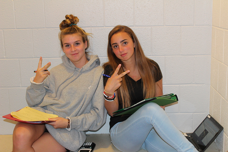 2 girls working on homework and giving the peace sign